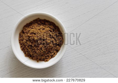 Ground Coriander Seeds In White Ceramic Bowl Isolated On White Wood Background From Above.