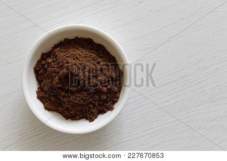 Ground Allspice In White Ceramic Bowl Isolated On White Wood Background From Above.