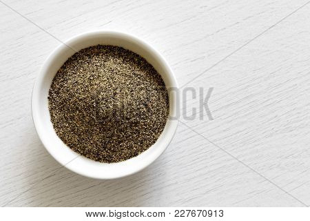 Finely Ground Black Pepper In White Ceramic Bowl Isolated On White Wood Background From Above.