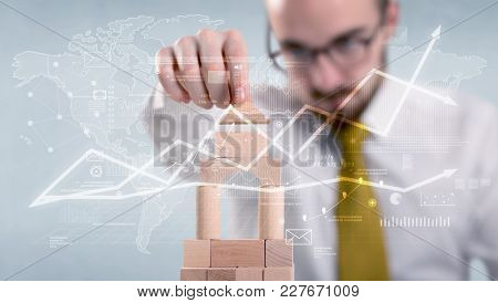 Young handsome businessman using wooden building blocks with data and calculations behind him