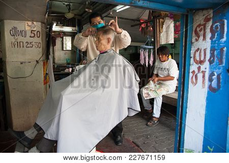 Bangkok, Thailand - December 4, 2007 : A Hairdresser Cuts The Hair Of His Client In An Old Hairdress