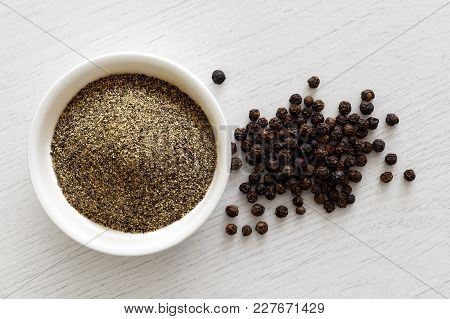 Finely Ground Black Pepper In White Ceramic Bowl Isolated On White Wood Background From Above. Black