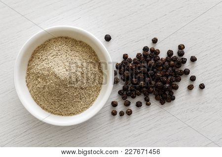 Finely Ground White Pepper In White Ceramic Bowl Next To Black Peppercorns Isolated On White Wood Ba