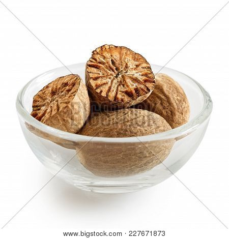 Dried Whole And Cut Nutmegs In Glass Bowl Isolated On White.