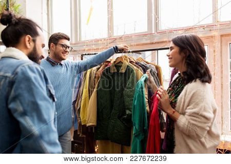 sale, shopping, fashion and people concept - friends choosing clothes at vintage clothing store