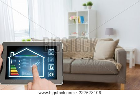 smart home and technology concept - close up of male hands pointing finger to tablet pc computer with house settings on screen over living room background