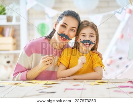 Funny family playing at home. Mother and her daughter girl with a paper accessories. Mom and child are holding mustache on sticks.