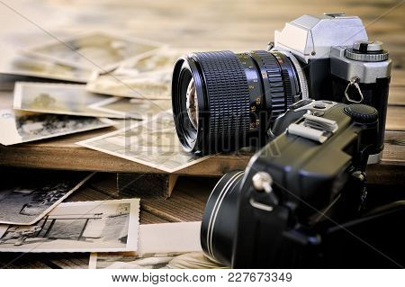 Closeup Of Vintage Photographic Prints, Film Camera And Digital Compact On Aged Wooden Background.