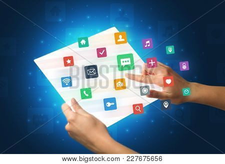 Young female hand holding a tablet with colorful mixed media icons