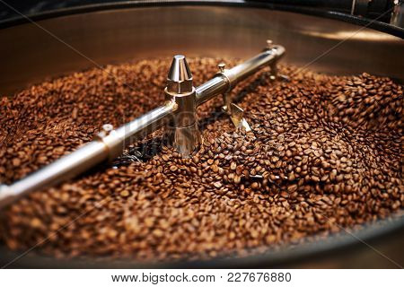 Stainless Steel Arms Mixing Freshly Roasted Coffee Beans In Large Stainless Steel Cooling Drum Where