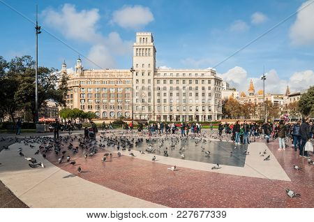 Barcelona, Spain - December 5, 2016: Tourists Feed The Pigeons On The Square Of Catalonia (placa De