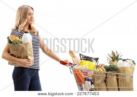 Young woman with a paper bag and a shopping cart filled with groceries isolated on white background