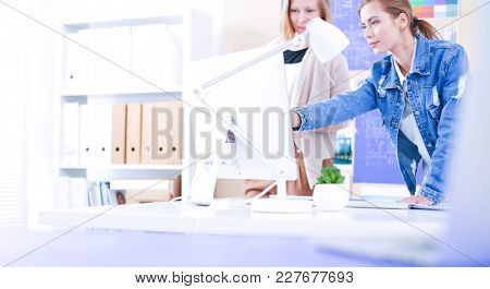 Two young woman sitting near desk with instruments, plan and lap