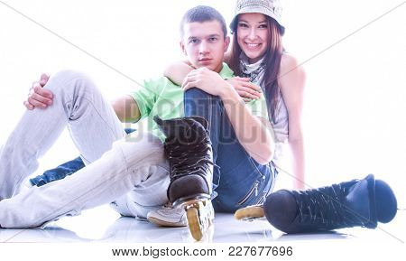 Young couple sitting on the floor , isolated on white background
