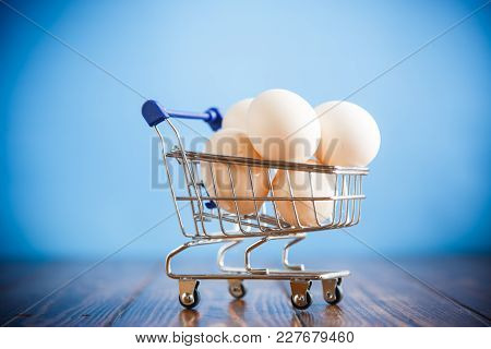 Shopping Cart Full With Eggs On A Blue Background