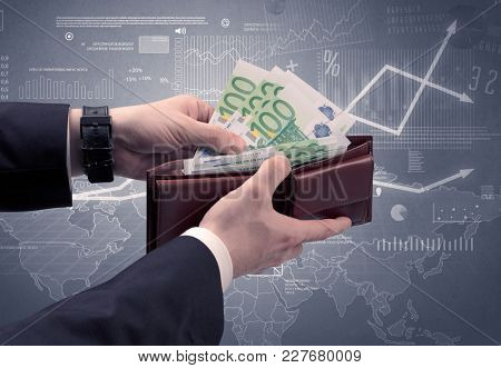 Businessman's hand takes out dollar from wallet with finance graphic on the background