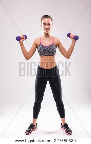 Portrait Of Young Happy Smiling Woman In Sportswear, Doing Fitness Exercise With Dumbbells Over Whit