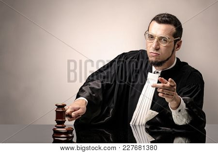 Young dashing judge in black gown making decision with no concept