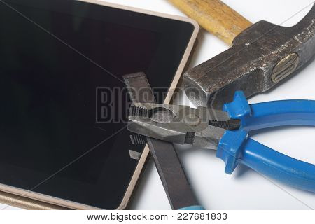 Tablet And Working Tools. On The White Surface Of The Table Is A Tablet, Skein, Chisel And Pliers. D