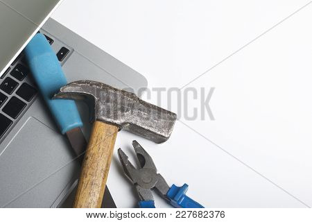Laptop And Work Tools. On The White Surface Of The Table Is A Tablet, Skein, Chisel And Pliers. Dest