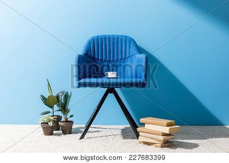 Comfy Blue Armchair With Cup Of Coffee In Front Of Blue Wall