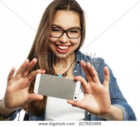 Pretty hipster girl taking selfie. Young and happy. Lifestyle concept.