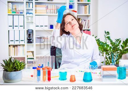 Girl Scientist Or Researcher Researching In The Laboratory. Different Reagent Flasks And Test Tubes