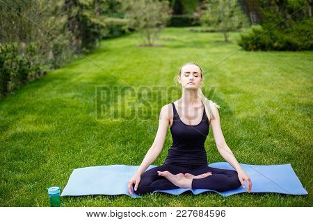Young Woman In Lotus Pose In The Park