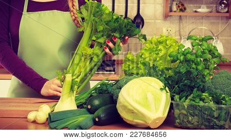 Woman In Kitchen With Many Green Leafy Vegetables, Fresh Produce On Table. Young Female Adding To He
