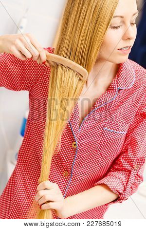 Woman Combing Brushing Her Long Smooth Hair In Bathroom With Wooden Comb. Girl Taking Care Refreshin