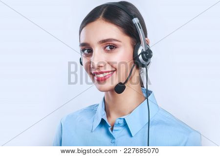 Smiling Customer Support Female Phone Operator In Headset, Against Grey Background. Consulting And A