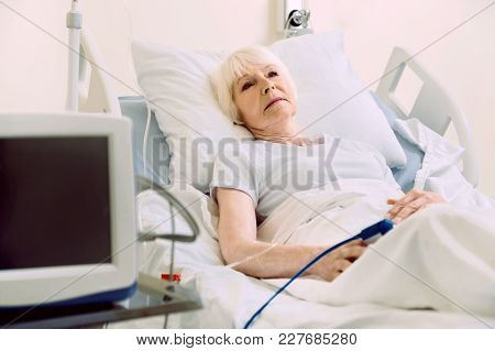 Stressful Life. Exhausted Elderly Woman Looking Into Vacancy While Lying In A Hospital Bed With A He