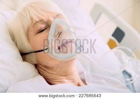 Medicine Is The Best Medicine. Ill Senior Woman Lying In A Hospital Bed While Wearing An Oxygen Mask