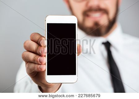 Close up of a businessman showing blank screen mobile phone isolated over gray background