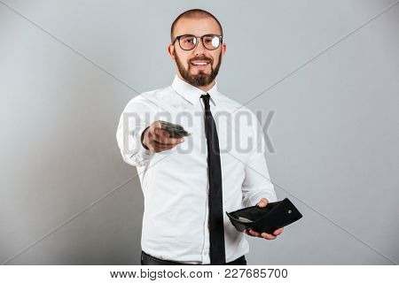Photo of mature man in glasses and suit giving money dollar cash on camera from wallet isolated over gray background