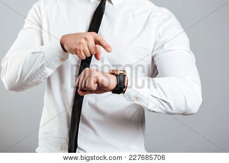 Cose up of a businessman pointing finger at his wristwatch isolated over gray background