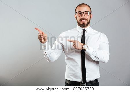 Photo closeup of content office worker in white shirt and eyeglasses smiling on camera and pointing fingers aside on copy space, isolated over gray background
