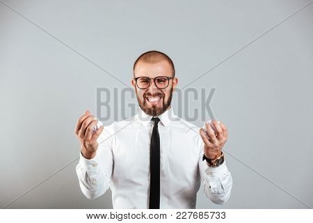 Annoyed mad business man in white shirt and eyeglasses crumpling papers in both balls isolated over gray background