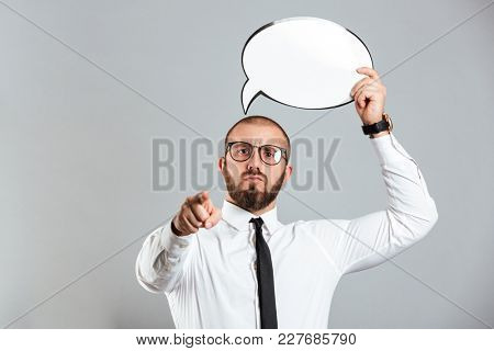 Portrait of a confident businessman holding empty speech bubble above his head and pointing finger at camera isolated over gray background