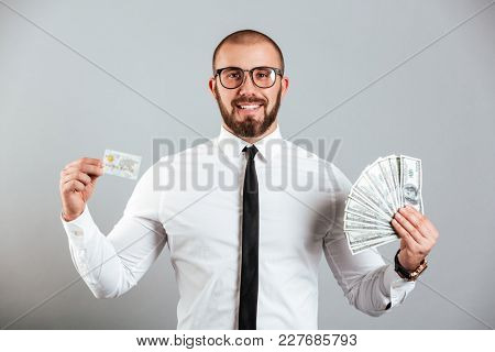 Photo of rich man 30s in glasses and tie showing credit card and fan of dollar bills isolated over gray background