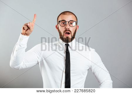 Image of smart caucasian man in white shirt and eyeglasses pointing finger upward on copy space or gesturing have idea isolated over gray background