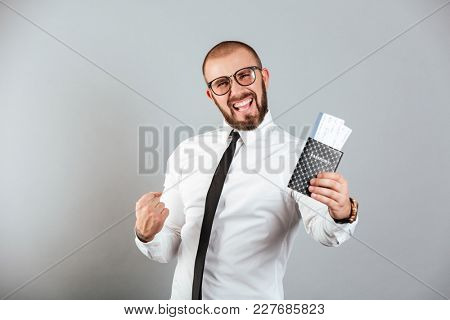 Photo of delighted businessman rejoicing his vacation while holding passport and tickets isolated over gray background