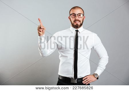 Photo of ambitious caucasian man in white shirt and eyeglasses smiling on camera and pointing finger upward on copy space isolated over gray background