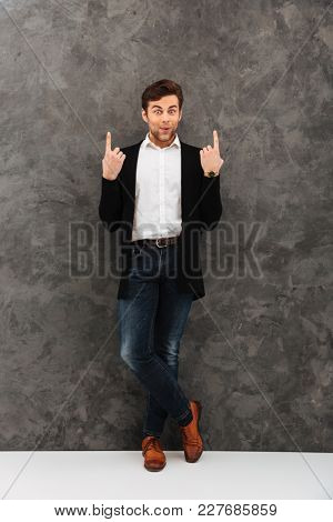 Image of shocked young businessman standing over grey wall background looking camera pointing.