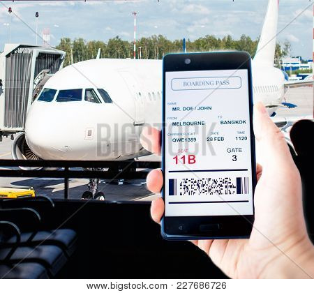 Man Hand Holding Mobile Phone With Mobile Boarding Pass. Boarding Pass On Phone Is Fake