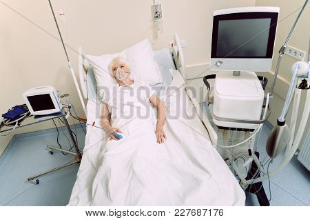 Having Some Health Problems. Top View On An Elderly Lady With An Oxygen Mask And A Heart Rate Medica