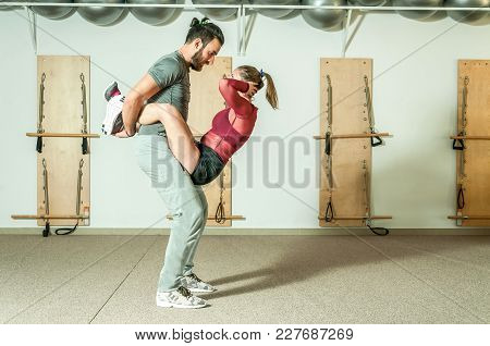 Young Handsome Fitness Couple In Love Abdominal Training While He Holding She For Her Legs, Selectiv