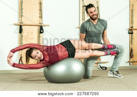 Handsome Male Personal Trainer With A Beard Helping Young Beautiful Girl For Aerobic Exercise In The