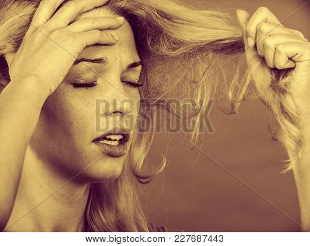 Haircare, Health Problem Concept. Unhappy Sad Woman Looking At Damaged Split Ends On Her Blonde Hair