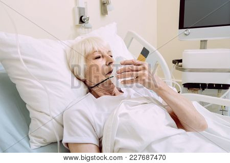 Serious Health Problems. Exhausted Retired Lady Looking Sad While Lying In A Hospital Bed And Holdin